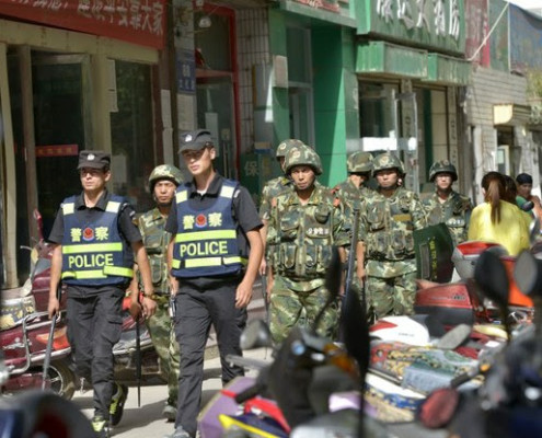 Chinese police officers and paramilitary policemen patrol a street in Kashgar city, July 23, 2014.  ImagineChina
