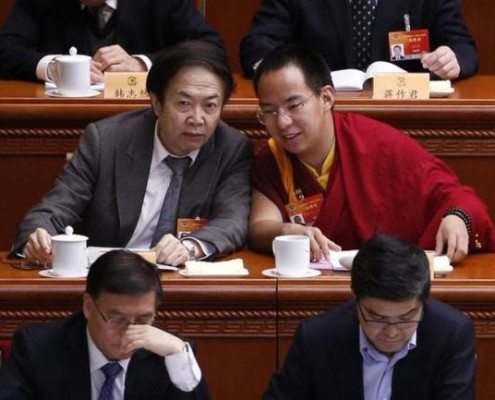 Gyaltsen Norbu (R), the 11th Panchen Lama, speaks with a delegate ahead of the opening of the third plenary meeting of Chinese People's Political Consultative Conference (CPPCC) at the Great Hall of the People in Beijing, March 11, 2015.  REUTERS/KIM KYUNG-HOON