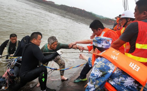 A survivor is helped from the overturned passenger ship in the Jianli section of the Yangtze River yesterday. The ship capsized after it was caught in a storm. Photo: Xinhua