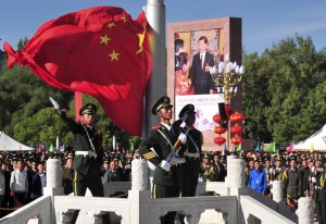 Chinese paramilitary police conduct a flag rising ceremony as thousands of people gather in front of the iconic Potala Palace in the regional capital Lhasa on September 8, 2015