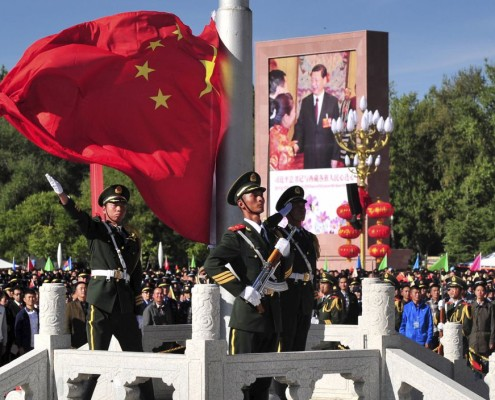 A paramilitary policeman unfurls a Chinese national flag at the celebrations event on Sept. 8.(Reuters/China Daily)