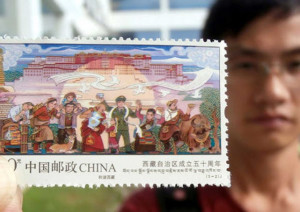 A Chinese stamp collector shows a stamp issued to mark the 50th anniversary for the establishment of Tibet autonomous region at a China Post Office in Suzhou city, East China's Jiangsu province. Photo: China Daily/ANN