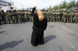 A local woman on a crutch shouts at Chinese paramilitary police in China's Xinjiang Autonomous Region.	(Reuters/David Gray)