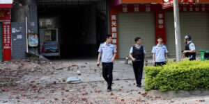[LIUCHENG: Chinese police officers walk past the scene of an explosion in Liucheng county in <a href=