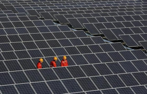 Workers walk among newly installed solar panels at a solar power plant in Zhouquan <a href=