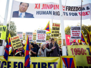 Human rights demonstrators stand beneath a protest banner bearing an image of Chinese <a href=